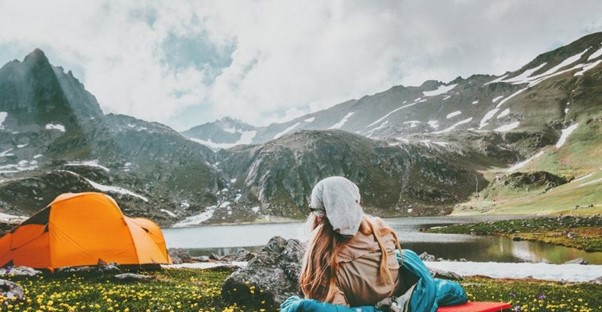 woman camping outdoors in mountains