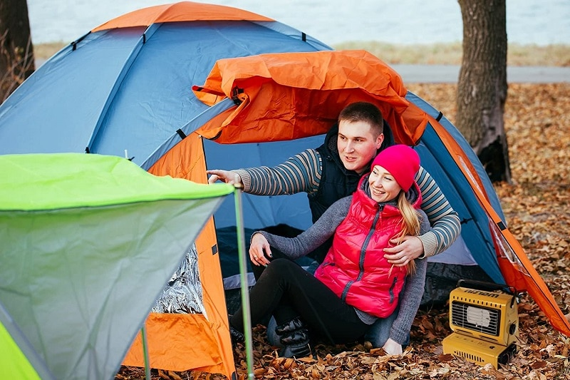 couple camping with tent heater