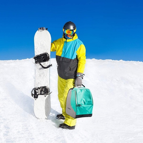 snowboarder carrying boots in bag